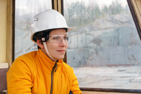 woman in a hard hat and goggles in the cab of heavy construction equipment Reklamní fotografie