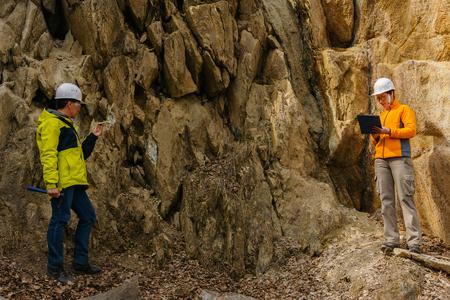 geólogos masculinos y femeninos toman una muestra del mineral y registran datos en un cañón Foto de archivo