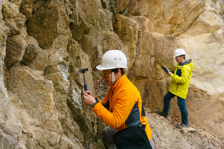 male and female geologists takes a sample of the mineral and record data in a canyon