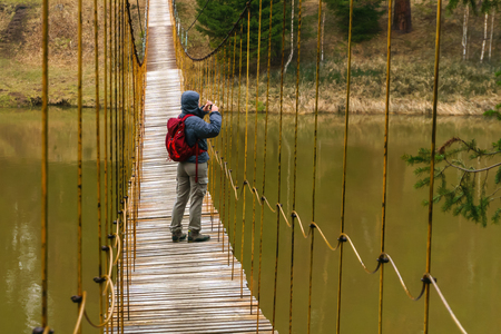 woman traveler takes a picture standing on a suspension bridge over the spring river Фото со стока