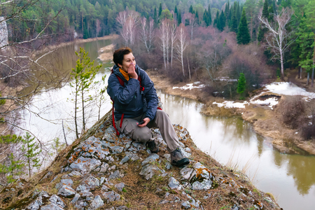 woman traveler sits on a cliff above the spring river in the forest and screams into the distance