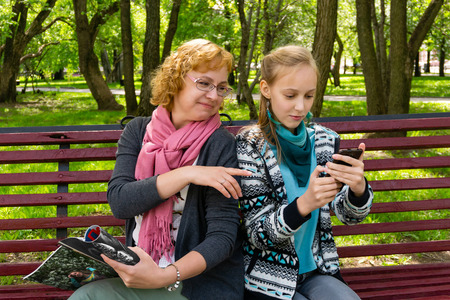 mother and teen daughter on a park bench are reading a paper and mobile electronic version of  some magazine