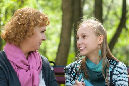 mother and teen daughter talking on a park bench