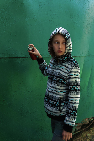 teen girl with spray paint looks around, about to write graffiti on the wall