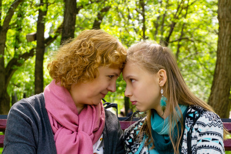 mother and daughter teenager confidentially communicate about something on a park bench, touching each other with their foreheads