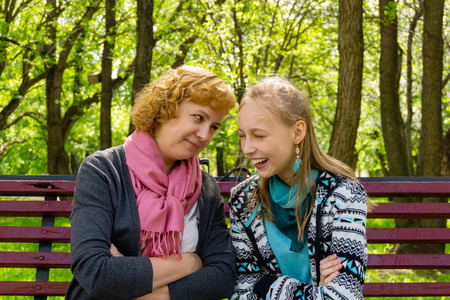 mother and teen daughter something on a park bench Stock Photo