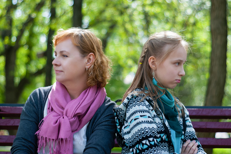 mother and teen daughter are sitting on a park bench in closed poses, turned away from each other, with an angry expression on their faces