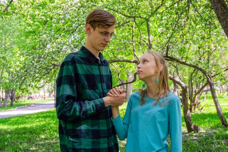 two teenagers, brother and sister, communicate outdoor in the park