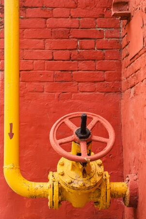 Yellow industrial gas pipeline with elbow and isolation valve with rotary handle against the background of a red brick wall Imagens