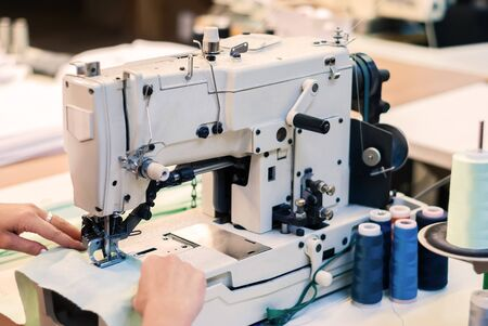 industrial overlock sewing machine and hands of seamstress at work in the garment factory