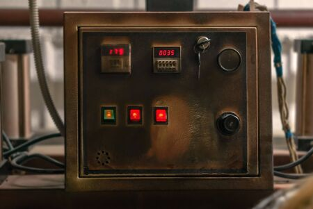 control panel of an old industrial heat press, darkened by time and high temperatures