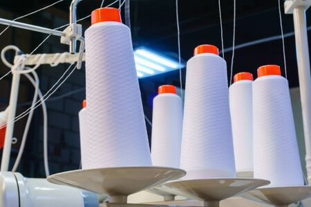 bobbins with white threads secured in an industrial sewing machine at the garment factory