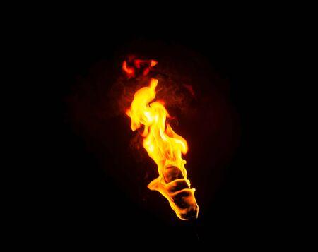 flamme d'une torche dans le noir sur fond noir, seul le feu est visible Banque d'images
