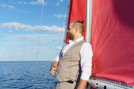 bearded man in a respectable vest looks into the distance, leaning against the mast of a sailboat in the sea