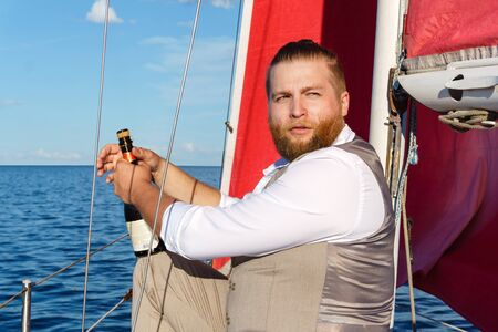 bearded man in a waistcoat with a bottle of sparkling wine next to the mast on a sailboat in the sea Фото со стока