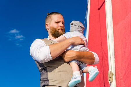 bearded man holding a baby in his arms against the background of blue sky and a ship mast with red sails