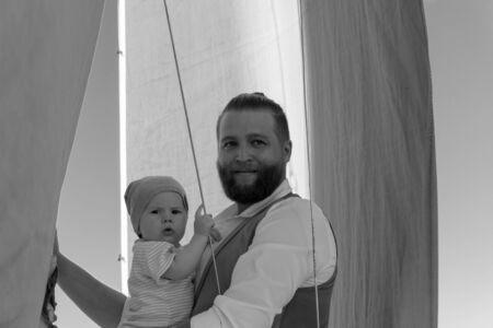 bearded man holding a baby in his arms against the background of sky and ship sails, monochrome