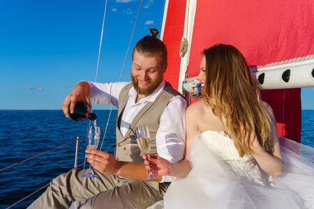 newlyweds in a wedding trip to the sea on a sailing yacht, pouring sparkling wine