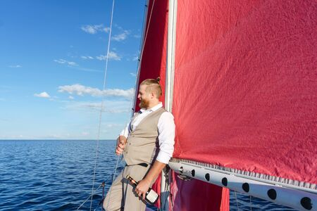 smiling bearded man in a waistcoat with a bottle of sparkling wine next to the mast on a sailboat in the sea
