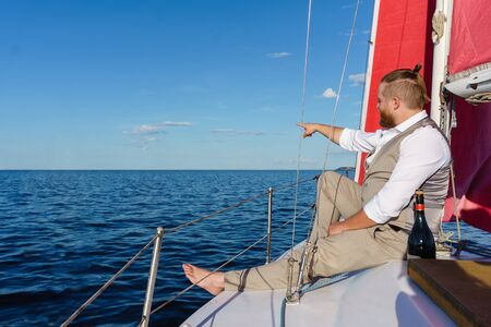 bearded man in a waistcoat sit relaxed next to the mast with a bottle of sparkling wine on a sailboat in the sea and points his finger to distance
