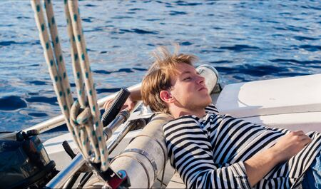 young male yachtsman resting aft of the yacht on a sunny day during forced inactivity during calm weather Standard-Bild