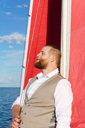 bearded man in a waistcoaton a sailboat in the sea leaned against the mast with a blissful smile on his face Stok Fotoğraf