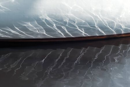beautiful reflections from the waves and sunlight on board a small sailboat moored in a wooded bay