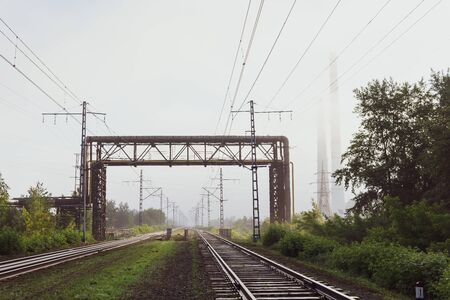 industrial landscape - railway tracks going into the morning mist, pipelines and chimneys in the fog