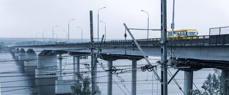 industrial landscape - road bridge over a wide river and railway wires in the foreground