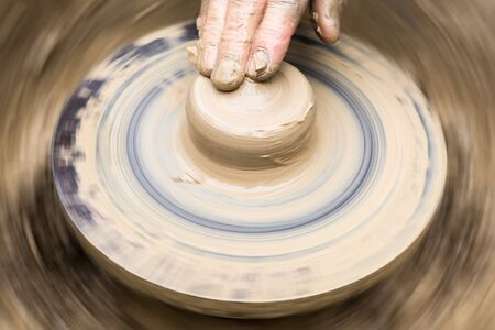 potter's fingers touch the shapeless piece of clay on the rotating wheel
