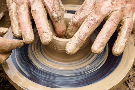 potter's fingers touch the shapeless piece of clay on the spinning wheel, giving it shape Stock Photo