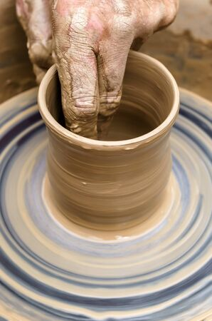 potter's hand mold pottery on a rotating wheel, close-up Stock Photo