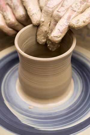 potter's hands mold pottery on a rotating wheel, close-up