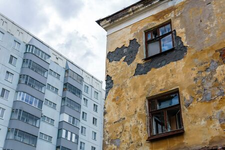 abandoned dilapidated house on the background of a residential multi-storey panel building