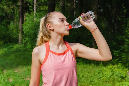 woman runner quenches thirst from a plastic bottle while jogging through the forest Banco de Imagens
