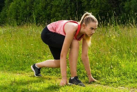 young woman in low start position before jogging on grass in park