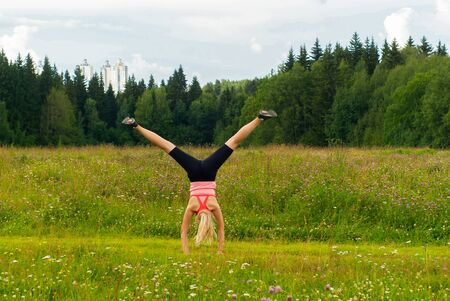 young woman doing somersault cartwheel outdoors in a meadow outside the city