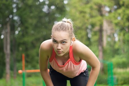 young woman is out of breath and makes a breather bent over while doing sports outdoors Stockfoto - 129819963
