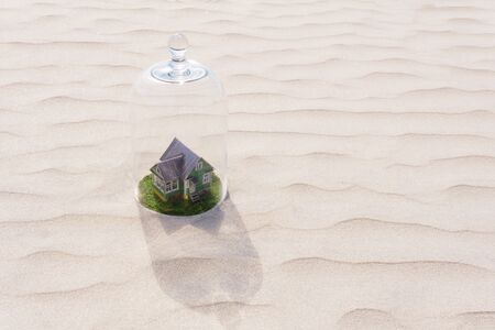 toy cardboard house with green lawn protected by a glass dome cloche among of a lifeless sand desert