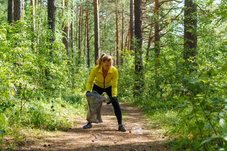 young woman collects litter in a garbage bag while jogging in a park