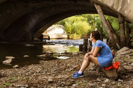 woman smokes while sitting alone under an old bridge on the banks of a city river