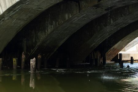 the stream flows under the old bridge with arched vaults and the remains of wooden piles