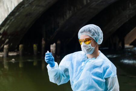 female ecologist or epidemiologist takes test-tube water analysis in a city river under an old bridge Stockfoto