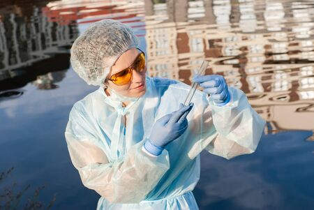 female epidemiologist looks at a test tube with water against the background of a water surface with a reflection of urban buildings