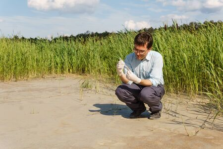 field researcher biologist examines a sample of soil in a test tube against a dry marsh