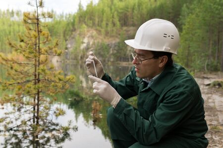 industrial ecologist or chemist takes a sample of water from a flooded quarry