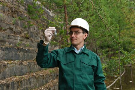industrial ecologist or hydrologist takes a sample of water from old quarry Stockfoto