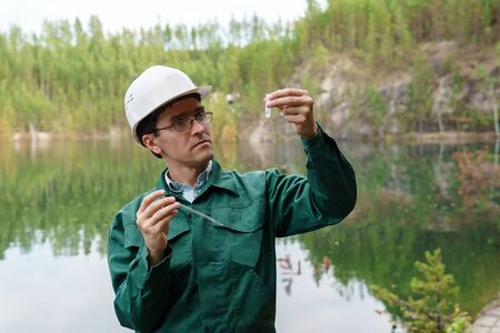industrial ecologist or hydrologist visually evaluates the response of a water sample from lake at the site of a flooded quarry Stockfoto - 129763353