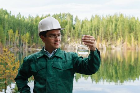 industrial ecologist or hydrologist visually evaluates the response of a water sample from lake at the site of a flooded mining pit Stockfoto