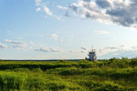 floodplain in the river delta and superstructure of tugboat visible above the grass